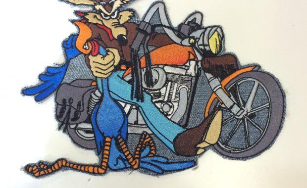 Parche con el coyote en moto agarrando al correcaminos